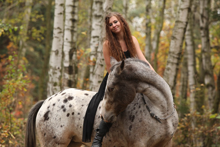 appaloosa: Young girl with appaloosa horse in autumn forest