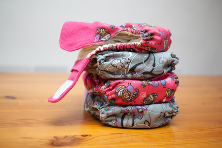 Stack of eco cloth diapers on a wooden table