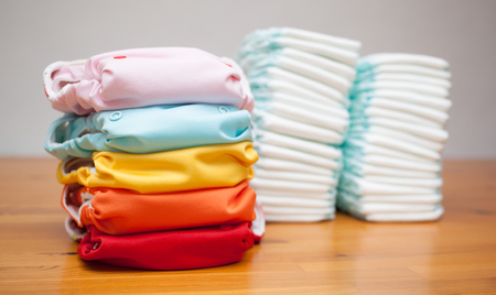 Stacks of disposable diapers and modern cloth diapers together Stockfoto