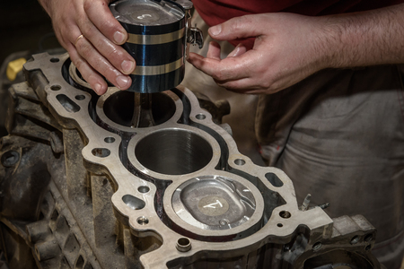 mechanic repairs the car engine in the workshop, install the piston