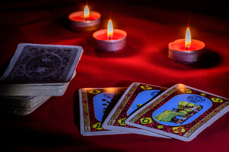 Tarot cards for the divination on the table in the light of candles