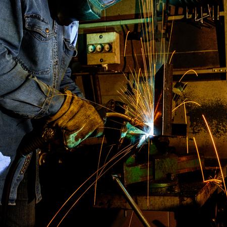 Welder at work welding steel structures in the workshop in production Imagens