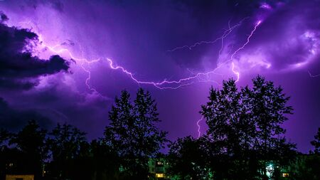 bright flashes of lightning during night thunderstorms, silhouettes of trees and houses against the dark blue sky