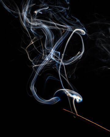 A trickle of white smoke from an incense stick on a black background