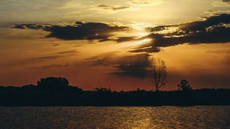 Landscape, sunset over the lake. Silhouette of the coastline and the sky with clouds