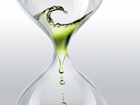 flowing: hourglass with green dripping water close-up Stock Photo
