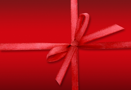 red ribbon bow on red background Stock Photo - 22497448