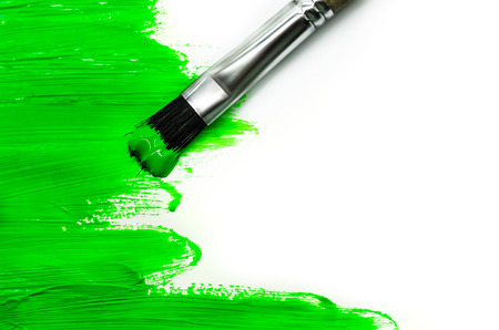 art and craft equipment: green paint brush on a white wall