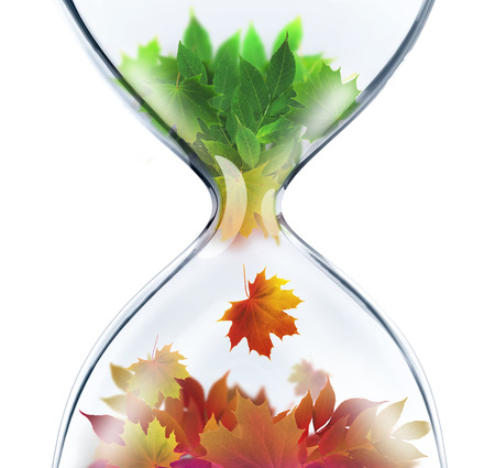 life change: From summer to autumn.The changing seasons concept with hourglass Stock Photo