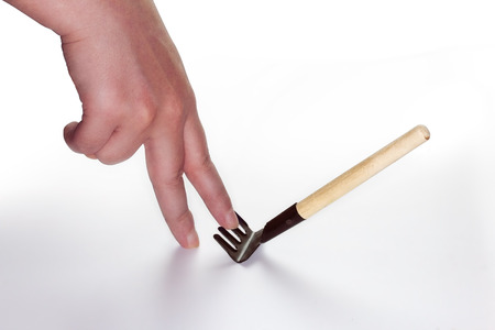 painfully: step on rake concept image with a hand Stock Photo