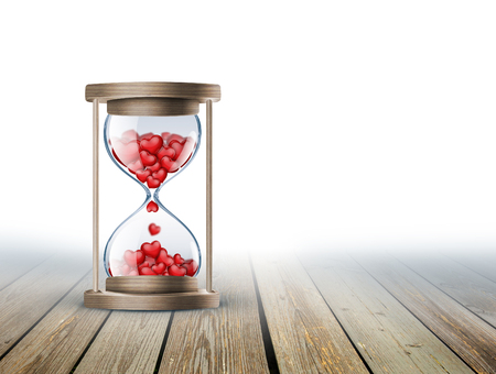 hourglass with red hearts on wooden surface 스톡 콘텐츠