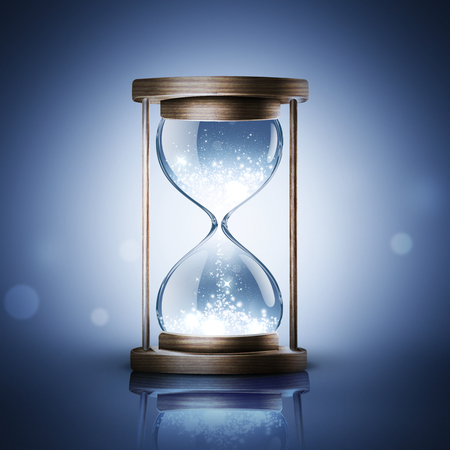 hourglass with shining light on dark blue background Stock Photo