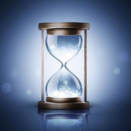 hourglass with shining light on dark blue background Foto de archivo