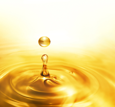 liquid gold: bright dripping oil close up as background