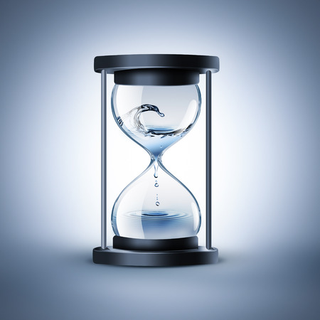instrument of time: hourglass with dripping water - time flows concept
