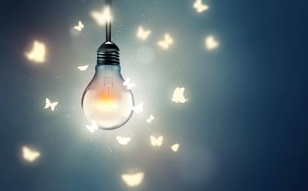 leuchtende Glühbirne und Schmetterlinge auf Licht fliegen Standard-Bild
