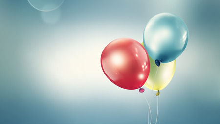 Three different colored balloons against a light blurred background