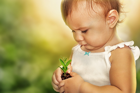 Portrait of a cute little child holding a plant sprout - concept of protecting the environment photo. Care of nature since childhood concept photos