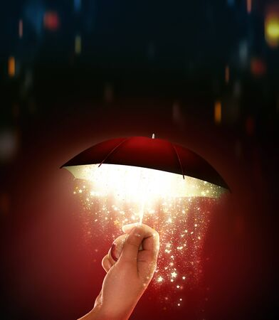 hand holds a umbrella with a magical glow 스톡 콘텐츠