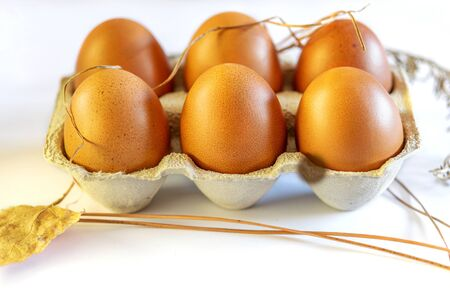 Some fresh raw eggs in the egg cage on the white background.