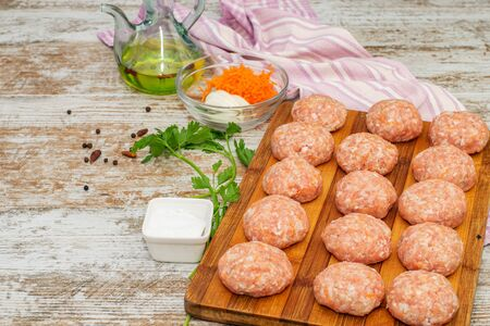 Fresh meatballs with spices and olive oil on the wooden natural table prepared for cooking.
