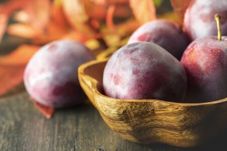 Some ripe purple plums in a wooden natural bowl, closeup, low key.