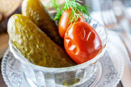 Salted marinated cucumbers and tomatoes with dill in the transparent glass bowl. Delicious traditional snack.  写真素材