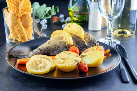 Black dish with fried fish dorada, slices of lemon, potatoes, carrot and little tomatoes cherry. Also there are cheese chips, black cutlery, wineglass, olive oil, a branch of eucalyptus on the dark table background. Festive decorated table.