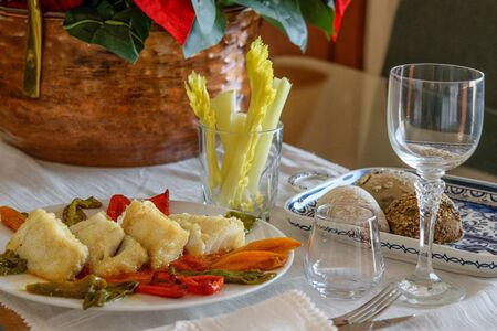 A table decorated for Christmas or New Year holiday. Big white dish with slices of fried cod fish and sweet bell peppers, some green in a glass and a plate with various buns on the festive table.