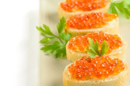 Red caviar on the slices of fresh white loaf with parsley on the white dish. White background.Healthy sea food.