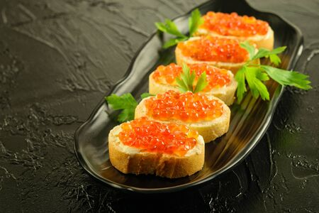Red caviar on the skices of fresh white loaf with parsley on the black dish. Black background. Stock fotó