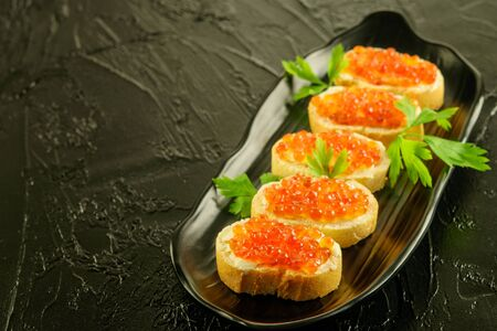 Slices of fresh white bread with butter and red caviar_ with parsley on the black dish and on the black background.  Stock fotó