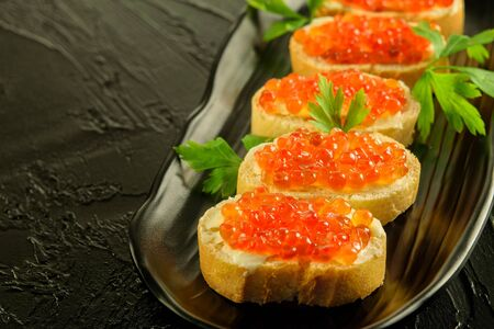 Sandwitches of fresh white bread with butter and fresh red caviar on the black dish, on the black background closeup.