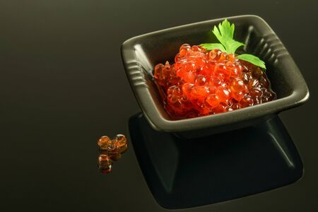 Red fresh caviar on the black platter, on the black reflective background. Healthy fresh food concept.