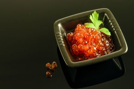 Red caviar with green parsley in the littles black bowl on the black reflective background. Healthy delicious food.  Stock fotó