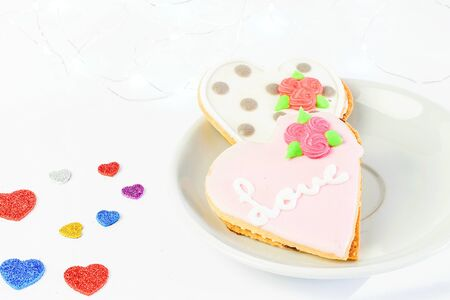 Sweet cakes on the white plate and on the white background with some little colorful hearts closeup. Sant Valentines day concept.