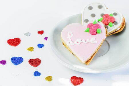 Two sweet glazed cakes in a from of hearts on the white plate and on the white background with some little colorful hearts closeup. Symbol of two lovers for Valentines day. 免版税图像 - 139602137