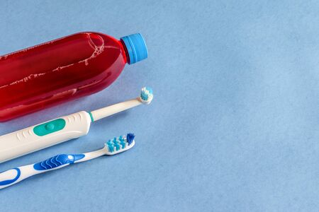 Personal products of hygien: antiseptic for mouth, toothbrushes closeup on the blue background, isolated. Personal hygienic remedies.