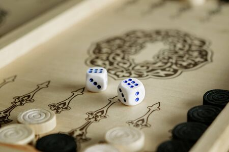 Backgammon table game, wooden board, dice and game chips closeup. Enjoying life, slow living. Leisure activities.