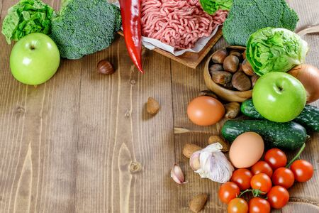 Ketogenic diet food background with a space for text. Vegetables, fruit, stuff meat on the wooden kitchen background. Healthy diet food.