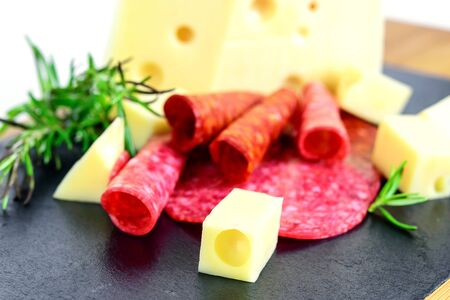 Slices of cheese, salami and chorizo closeup, macro. Fast food for snack.  Stock Photo