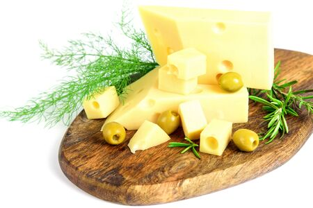 Emmental cheese, olives and fresh green dill with rosemary on the wooden cutting board, on the white background. Healthy calcium food.