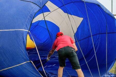 European Festival Balloon in Spain, Igualada. Worker prepares balloon for Balloon competition.