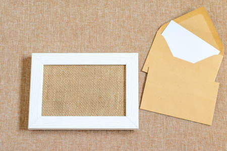 Desktop mock up with white wooden picture frame, envelopes on the textured burlap cloth. Zero waste, eco friendly objects. Top view, copy space. Mock up base for any design purposes.