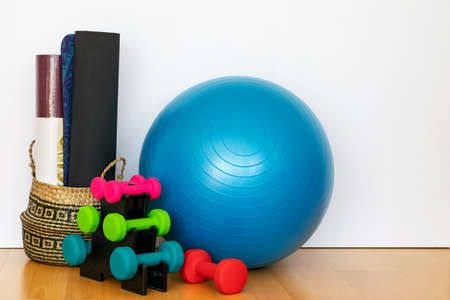 Composition of fitness dumbbells, mats and big fitness ball on the floor. Sport accessories for going in for fitness at home. Sport and relax,welness concept. Standard-Bild