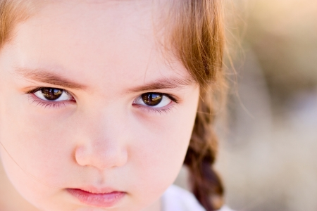Portrait of angry little girl with serious eyes photo