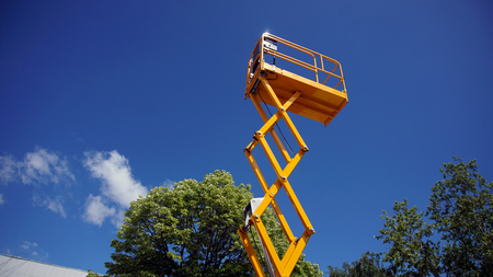 Scissor lift platform with hydraulic system at maximum height range painted in orange colors, large construction machine, heavy industry, white clouds and blue sky on background Banque d'images - 95662309