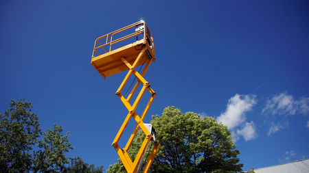 Scissor lift platform with hydraulic system at maximum height range painted in orange colors, large construction machine, heavy industry, white clouds and blue sky on background