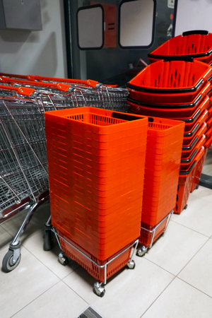 Rows of aligned shopping carts and red baskets.