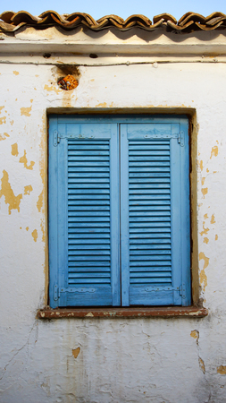Blue window shutters on a yellow building  Banque d'images